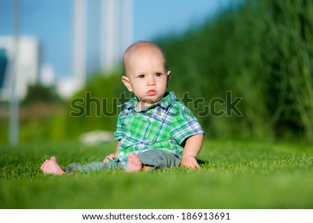 little cute kid in the spring or summer park sitting on the grass in sunshine day