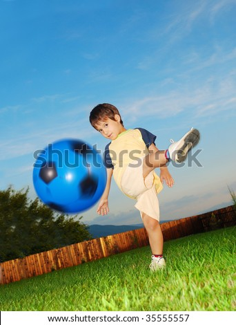 Little cute kid is hitting ball by his foot