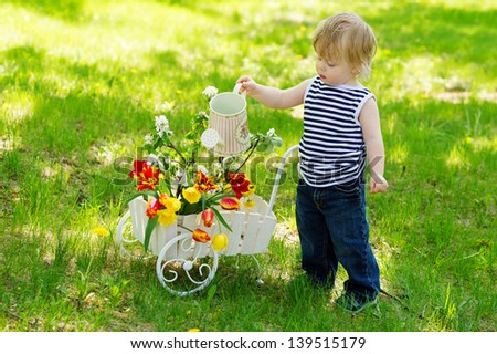 Little cute kid on the grass lawn with watering spring flowers in the wooden decorative wheelbarrow