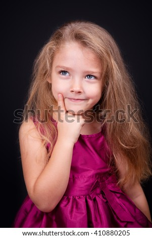 Little cute pensive girl in a bright pink dress on a black background in the studio - stock photo