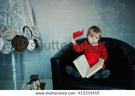 Little cute princess girl sitting on a chair, read old book and takes the crown from the head