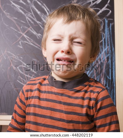 little cute real boy screaming and crying at school near blackboard close up - stock photo