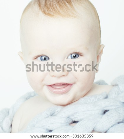 little cute red head baby in scarf all over him close up isolated, adorable kid winter clothers - stock photo