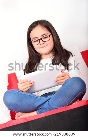 Little cute schoolgirl learning with a Tablet PC at home - stock photo