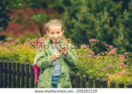 little cute schoolgirl with a school backpack on the background of flowers on the street - stock photo