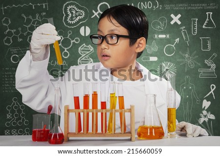 Little cute scientist doing experiment and looking at chemical fluid in the laboratory - stock photo