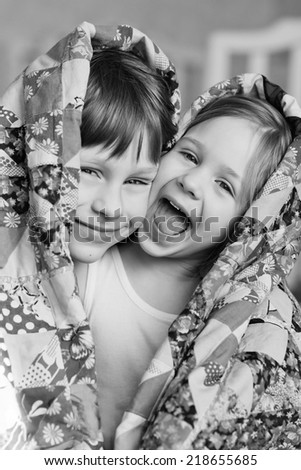 Little cute smiling children - brother and sister  - looking out from the blanket or  counterpane close up. Black and white.  - stock photo