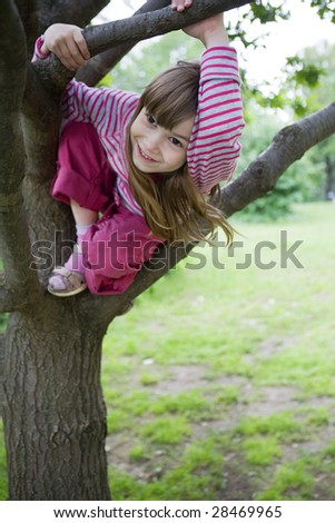 little cute smiling girl  seven years old with long hair climb on tree. Summer time - stock photo