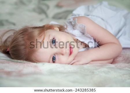 Little cute smiling girl with blue eyes lying on a bed in a white dress - stock photo
