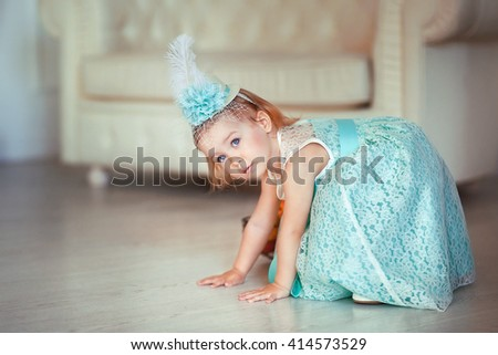 Little cute toddler girl in an elegant green dress and hat joking  and playing. Adorable kid with beautiful blue eyes. - stock photo