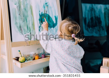 Little cute toddler girl painting with gouache paints on the balcony  - stock photo
