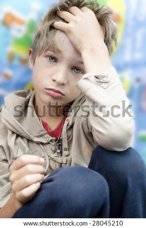 little cute upset boy sitting touch head with hand - stock photo