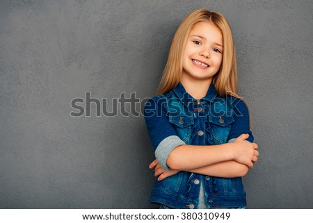 Little cutie. Cheerful little girl holding arms crossed and looking at camera with smile while standing against grey background - stock photo