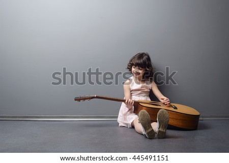 Little cutie discovers acoustic guitar with an interest for music. Beautiful girl smiles and looks on the musical instrument. Adorable child sits on the floor in the studio. - stock photo