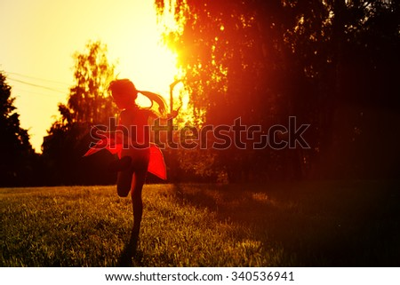 Little cutie girl in a red dress dancing in the sunset