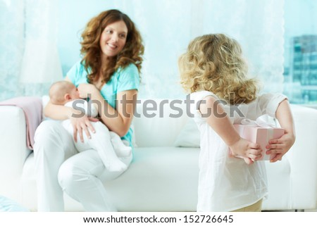 Little cutie holding a gift-box behind the back to surprise her mom - stock photo