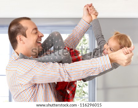 Little daughter climbing up on father, having fun, both laughing. - stock photo