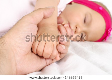 Little daughter holds his father's hand while sleeping - stock photo
