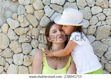 Little daughter hugging her mother. Family portrait. Smiling young woman and child on the background of an old stone wall. - stock photo
