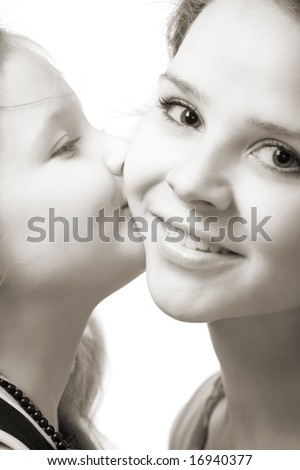 little daughter kissing her beautiful young mother