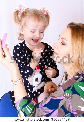 little daughter mum makes makeup. Mom and daughter playing. Daughter and mother putting makeup - stock photo
