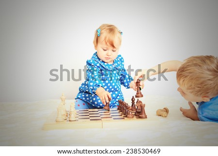 little daughter playing chess with brother indoors - stock photo