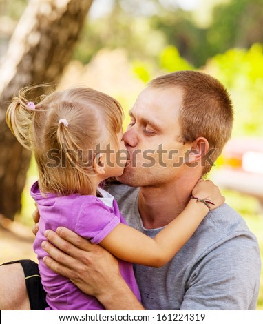 Little daughter tender kiss her father - stock photo
