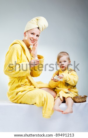 little daughter with her young mother  making up - stock photo