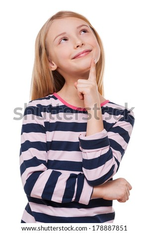 Little daydreamer. Cheerful little girl holding finger on chin and looking away while standing isolated on white - stock photo