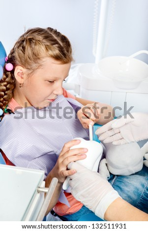 Little dentist patient playing with toy tooth