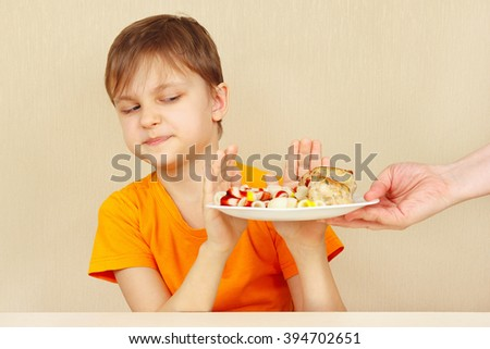 Little disaffected boy refuses to eat a pasta with cutlet - stock photo