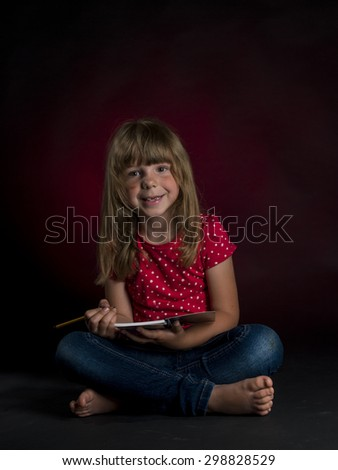 little disheveled girl with pencil on the black background - stock photo