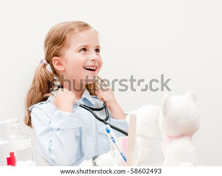 Little doctor examining teddy bear (no-name toys) - stock photo