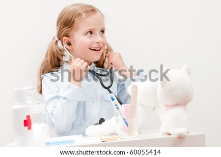 Little doctor examining teddy bear (no-name toys) - stock photo