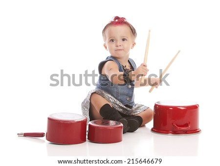 Little drummer girl.  Adorable toddler dressed as a punk rock star and playing with drum sticks.  Isolated on white.