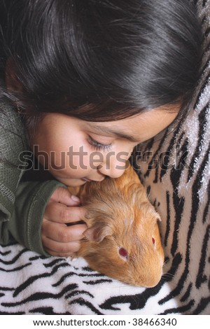 Little east indian girl and guinea pig - stock photo