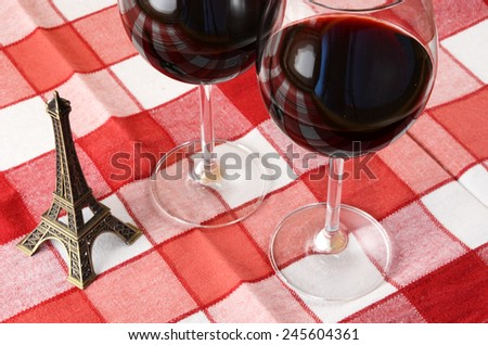 Little Eiffel tower and a pair of wineglasses on the table  - stock photo