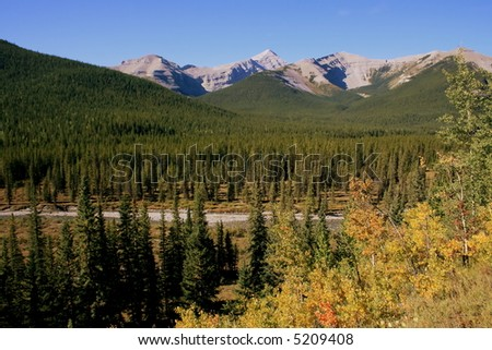 Little Elbow River Valley in Kananaskis country (west of Calgary, Alberta, Canada; mountains; river valley; fall colours in the trees; crisp clear day; blue skies - stock photo