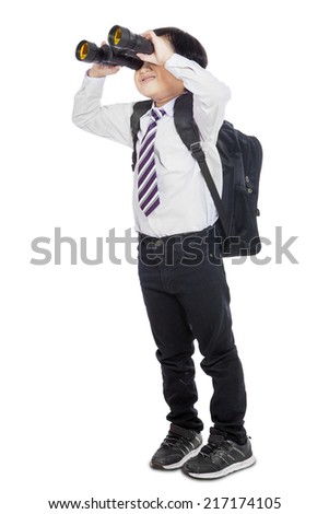 Little elementary school student using binoculars in studio, isolated over white - stock photo