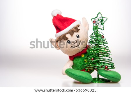 Little elf handmade toy christmas decoration with christmas tree on white background