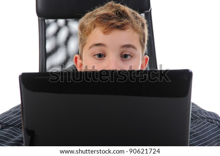Little emotional boy sits at a computer at a desk in a bright office. Isolated on white background - stock photo