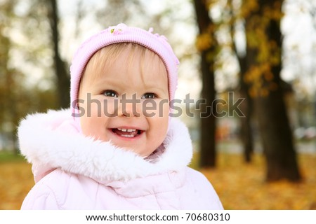 Little emotional girl on the park background