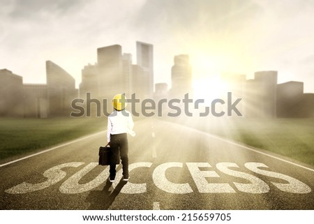 Little engineer looking for success and standing on the highway of a skyscraper with cityscape - stock photo