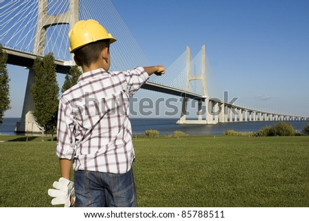 "Little ""engineer"" pointing to a bridge - stock photo"