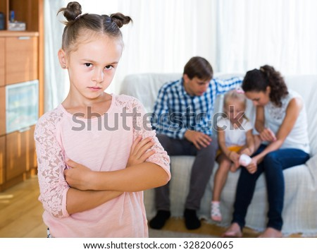 Little european girl sad because of jealous younger sister to parents. focus on girl - stock photo