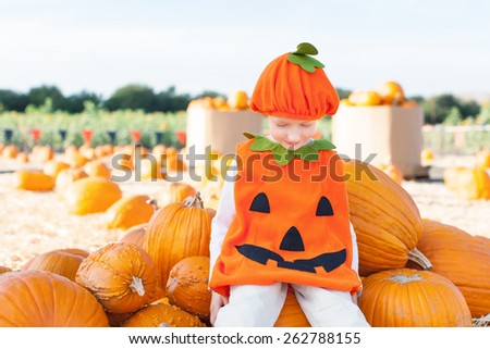 little excited kid in halloween pumpkin costume enjoying time at pumpkin patch  - stock photo