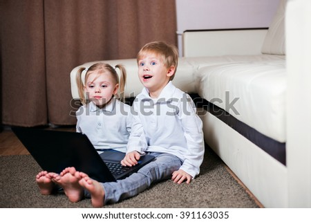 little fair-skinned blond children, a boy and a girl with pigtails sitting with a laptop on the floor, smiling, stormy emotions