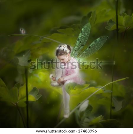 Little fairy between leafs in the garden - stock photo