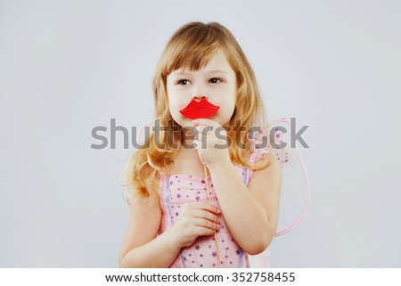 Little fairy, with curly blond hair, wearing on pink dress, and wings on her back, posing with paper lips on white background, in studio, waist up