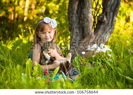 Little fanny girl playing with a cat in the park